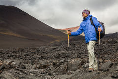 Young traveler on a background of volcanic rock. Stock Photography