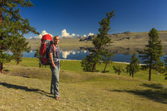 Young traveler with a backpack on the background of the lake Royalty Free Stock Photo