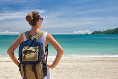 Young traveler with backpack enjoying view stunning tropical beach. Happy young traveler with a backpack, enjoying the view of a tropical beach on a background royalty free stock image