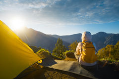 Young traveler with backpacker enjoying sunrise view at summit t Royalty Free Stock Photo
