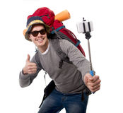 Young traveler backpacker taking selfie photo with stick carrying backpack ready for adventure. Young attractive  backpacker tourist taking selfie photo with Stock Images