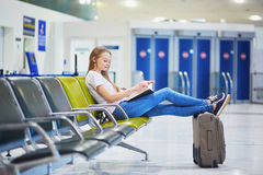 Young travelerin international airport reading a book while waiting for her flight Stock Images