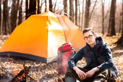 A young traveler in the forest is resting near the tent and cooked breakfast in nature royalty free stock image