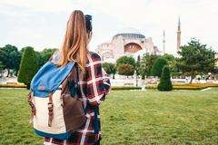 A young traveler girl with a backpack in Sultanahmet Square next to the famous Aya Sofia mosque in Istanbul in Turkey.  Stock Photo