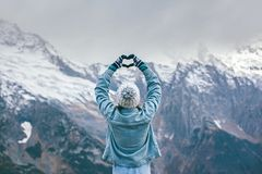 Free Young Traveler Girl In Gloves Standing Over Mountain Peaks And Making Heart By Hands Royalty Free Stock Image - 163267936