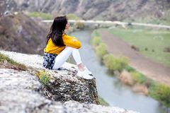 A young traveler girl sit on the top of valley. Young girl love wild life, travel, freedom. Travel Tourist Happy Woman. Travel and. Woman Enjoying Nature. Travel royalty free stock images