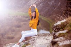 A young traveler girl sit on the top of valley. Young girl love wild life, travel, freedom. Travel Tourist Happy Woman. Travel and. Woman Enjoying Nature. Travel royalty free stock photos