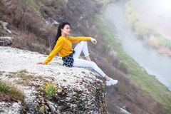 A young traveler girl sit on the top of valley. Young girl love wild life, travel, freedom. Travel Tourist Happy Woman. Travel and. Woman Enjoying Nature. Travel stock photo