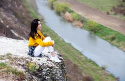 A young traveler girl sit on the top of valley. Young girl love wild life, travel, freedom. Travel Tourist Happy Woman. Travel and. Woman Enjoying Nature. Travel stock image