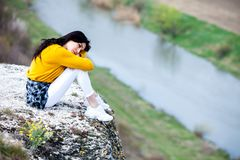 A young traveler girl sit on the top of valley. Young girl love wild life, travel, freedom. Travel Tourist Happy Woman. Travel and. Woman Enjoying Nature. Travel royalty free stock photo