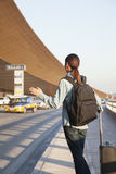Young traveler hailing a taxi at airport Stock Photo