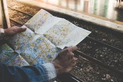 Young traveler holding travel map outside train window on a platform in the train station. Concept travel by train Royalty Free Stock Images