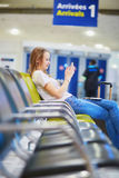 Young traveler in international airport checking her mobile phone while waiting for her flight. Young traveler with carry on luggage in international airport Royalty Free Stock Photos