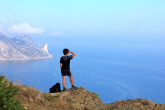 Young traveler looks at the beautiful seascape from the mountain Royalty Free Stock Images
