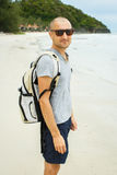 Young traveler man with backpack walking alone at seaside. Stock Photo