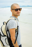 Young traveler man with backpack walking alone at seaside. Royalty Free Stock Image