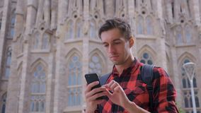 Young traveler man in checkered shirt walking in the Barcelona city and using smartphone, male traveling at Spain, slow. Young traveler man in red shirt walking stock video