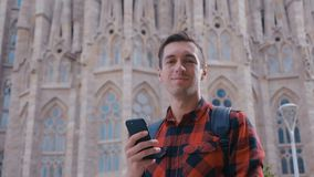 Young traveler man in checkered shirt walking in the Barcelona city and using smartphone, male traveling at Spain, slow. Young traveler man in red shirt walking stock video footage