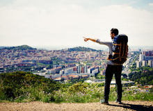 Young traveler man discovers a new city in his foot travel. Young hiker on the mountains royalty free stock images