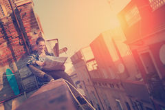Young traveler man sitting on the edge on high roof with map, backpack and skateboard. Brave and young traveler man sitting on the edge on high roof with map Royalty Free Stock Photography
