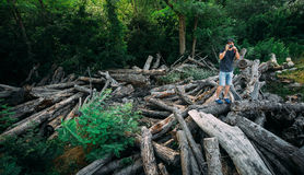 Young Traveler Man Stands On Logs And Takes Photos On Smartphone Camera With Copy-Space Left stock photos