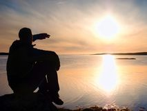 Young traveler man at sunset. Tourist  sitting on the cliff above lake Stock Photography