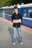 Young traveler with a map. Young traveler standing near the train and sees a map Stock Photography