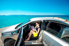 Young traveler with map sitting in the car. Young woman traveler sitting with paper map in the car and looking where to go on blue sea background Stock Photography