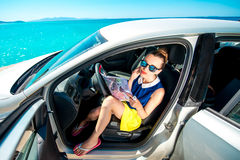 Young traveler with map sitting in the car Stock Image