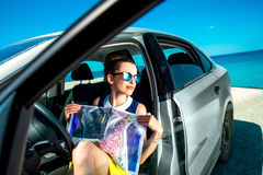 Young traveler with map sitting in the car royalty free stock photo