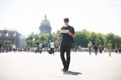 Young traveler with map in the street. Young handsome traveler man with backpack wearing casual clothes and cap looking at map, searching for direction while Royalty Free Stock Image