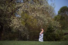 Young traveler pregnant woman walking, running, turning around and enjoys her leisure free time in a park with stock photo