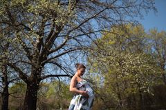 Young traveler pregnant woman walking, running, turning around and enjoys her leisure free time in a park with stock photography