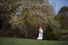 Young traveler pregnant woman walking, running, turning around and enjoys her leisure free time in a park with royalty free stock photo