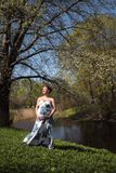 Young traveler pregnant woman walking, running, turning around and enjoys her leisure free time in a park with royalty free stock image