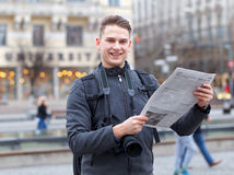 Young traveler at a public square reading newspaper Royalty Free Stock Photo