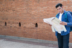 Young traveler reading map. asian man wearing blue shirt and jea Stock Image