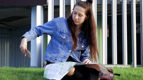 Young traveler resting on the lawn, looking at the map and navigation stock video