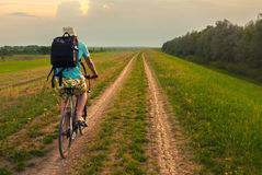 Young traveler riding bicycle in summer. Young traveler riding bicycle on country road stock photos
