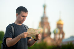 Young traveler sightseeing with map. Portrait of young handsome traveler man with backpack wearing casual clothes looking at map in front Church of the Savior on Stock Photos