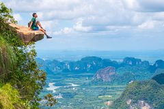 Young traveler sits on a rock that overhangs the abyss, with a beautiful landscape - Khao Ngon Nak Nature Trail in Krabi, Thailand