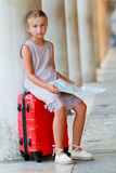 Young traveler sitting on suitcase with city plan, Venice, Italy Royalty Free Stock Photography