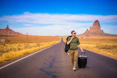 Young traveler with a suitcase walking on a road in Arizona Royalty Free Stock Photos