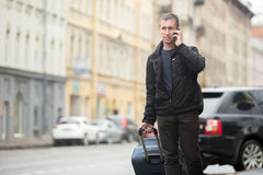 Young traveler talking on mobile phone in the street. Young smiling handsome man with luggage bag walking on rainy city street with busy traffic holding Stock Photos