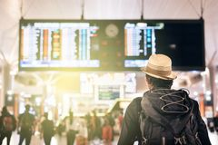 Young traveler or tourist looking at airport time board for flight schedule royalty free stock photo