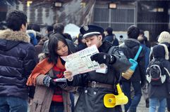 Young traveler and friendly tourist police. Tourist lost her way during city tiur in Sapporo , Japan. , She  brought the map to request assistance from a Stock Photo