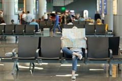 Young traveler tourist woman covering with paper map, search route, waiting in lobby hall at international airport. Passenger traveling abroad on weekends royalty free stock image