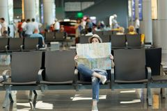Young traveler tourist woman covering with paper map, search route, waiting in lobby hall at international airport. Passenger traveling abroad on weekends royalty free stock photos