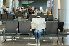 Young traveler tourist woman covering with paper map, search route, waiting in lobby hall at international airport. Passenger traveling abroad on weekends stock photography