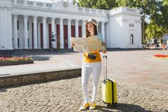 Young traveler tourist woman in yellow summer casual clothes, hat with suitcase looking on city map search route in city. Outdoor. Girl traveling abroad on royalty free stock image